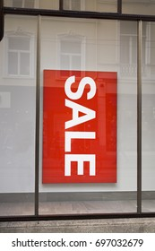 Big red sign Sale in shop window. Red rectangle with sale inscription sticked on the shop window