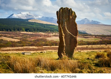 A big red standing stone on Machrie Moor on the Isle of Arran, Scotland. Some freshly fallen snow on Beinn Tarsuinn (826m) and Goatfell (874m).