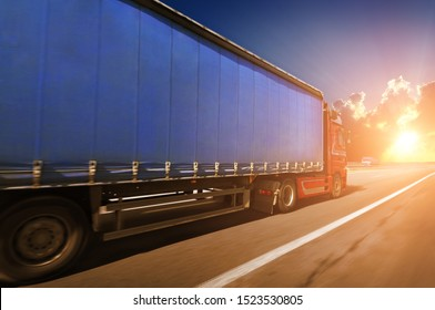 A big red truck and blue trailer with space for text driving fast on the countryside road against a night sky with a sunset