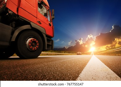 Big red truck on the countryside road against night sky with sunset