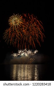 Big and rich orange and yellow stars with crackling effect from fireworks over Brno's Dam with lake reflection