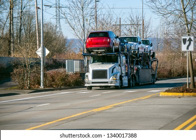 Big rig American classic bonnet semi truck with industrial car hauler semi trailer driving on local autumn road with yellow trees going to point of destination for unloading delivered vehicles