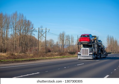 Big rig American model bonnet long haul car hauler semi truck with chrome custom bumper transporting different cars on two level semi trailer and driving on autumn road with bare trees