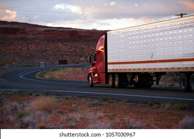 Big rig American modern red semi truck fleet with refrigerator semi trailer going on winding road with red rocks hills of Arizona landscape in twilight with sunlight clouds