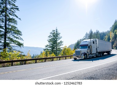 Big rig American powerful white classic semi truck transporting cargo in refrigerated semi trailer on winding autumn road in Columbia River Gorge in Washington
