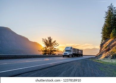 Big rig American white long haul powerful semi truck transporting boxes with fruits on flat bed semi trailer on straight evening road with scenic sunset in Columbia River Gorge