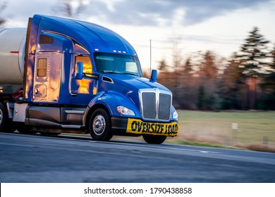 Big rig blue bonnet long haul industrial professional semi truck with sign oversize load on the front bumper transporting cargo in long tank semi trailer driving on the road with sunset
