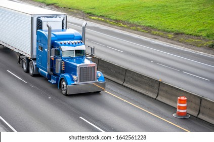 Big rig blue classic powerful diesel long haul semi truck transporting frozen commercial cargo in corrugated refrigerated semi trailer running on the wide divided highway road with concrete fence
