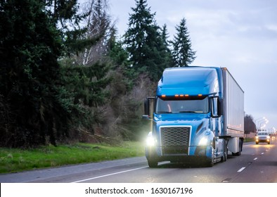 Big rig blue industrial diesel semi truck with grille guard transporting commercial cargo in dry van semi trailer running on the evening wet road with rain with turned on headlights