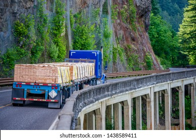 Big rig blue long haul semi truck with two flat bed semi trailers transporting industrial lumber boards running on the winding road with bridge around the mountain rock and the abyss on the sides