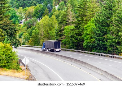 Big rig blue low cab semi truck for reduce air resistance and improve aerodynamic performance transporting covered black dry van semi truck on turning road with green trees in Columbia Gorge
