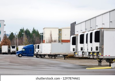 Big rig blue semi truck and refrigerated semi trailers standing in row in warehouse dock for loading and unloading commercial cargo and continuing go to the destination according to schedule