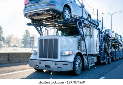 Big rig car hauler professional bonnet powerful semi truck transporting cars on two levels industrial semi trailer driving on winter frosty road with frost grass and trees on roadside