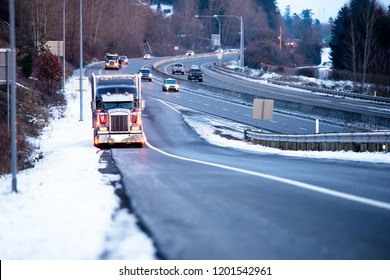 Big rig classic American fleet bonnet semi truck with head light turned on and refrigerated semi trailer standing on the shoulder of the highway exit in snow winter weather