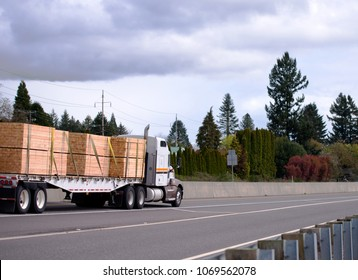 Big rig classic American idol semi truck tractor with day cab for local commercial cargo deliveries transporting stock of lumber wood on flat bed semi trailer on wide highway driving to destination