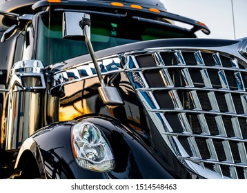 Big rig classic American idol black industrial semi truck with chrome grille and commercial cargo in dry van semi trailer standing on the truck stop parking lot at twilight time reflection sunlight