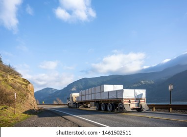 Big rig classic American powerful white semi truck with flat bed semi trailer transporting commercial cargo running on the road along railroad and river in Columbia Gorge area with mountain ranges