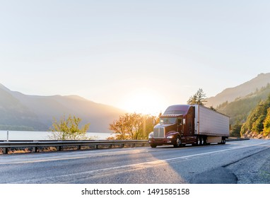 Big rig classic American powerful brown semi truck with refrigerated semi trailer transporting frozen goods running on the road along railroad and river in Columbia Gorge area with mountain ranges