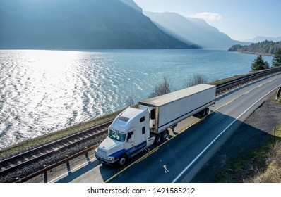 Big rig classic American powerful white semi truck with refrigerated semi trailer transporting frozen goods running on the road along railroad and river in Columbia Gorge area with mountain ranges