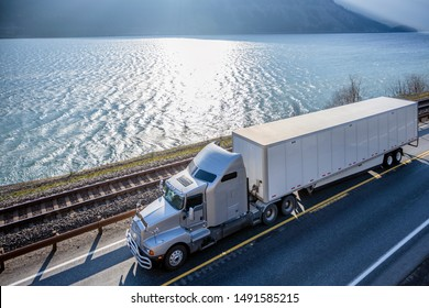 Big rig classic American powerful gray semi truck with dry van semi trailer transporting commercial cargo running on the road along railroad and river in Columbia Gorge area with mountain ranges