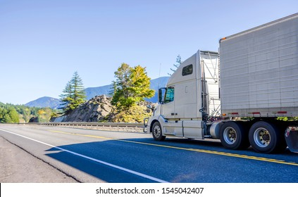 Big rig classic blue pro American bonnet semi truck with vertical exhaust pipes transporting frozen cargo in refrigerated semi trailer running on the mountain road with rock cliffs and autumn trees