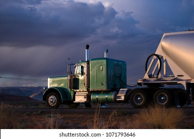 Big rig classic green semi truck with capacity compartment behind of tractor cab transporting bulk semi trailer carries cargo on the Arizona road in twilight with sunshine rays