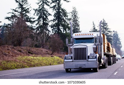 Big rig classic powerful semi truck with tall pipes and illumination light carry lumber wood as stacks of boards on two flat bed semi trailers on the straight road with trees background at sunny day