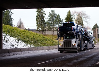 Big rig classic white car hauler semi truck transporting cars on special two-storey semi trailer going by highway under bridge in winter weather with snow on the shoulder grass