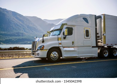 Big rig classic white pro American bonnet semi truck with refrigerator unit transporting frozen cargo in refrigerated semi trailer running on the mountain road with rock cliffs and autumn trees