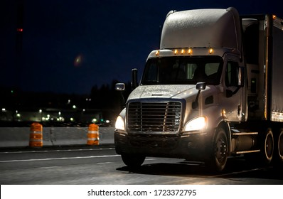 Big rig day cab heavy-duty diesel semi truck with roof spoiler transporting commercial cargo in semi trailer running on the wet raining highway road at dark night time with turned on headlight
