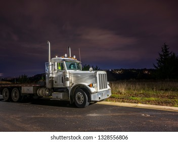 Big rig day cab semi truck with flat bed semi trailer standing on the parking lot in dark night time waiting for loading and possibility of continuing to destination according to approved schedule