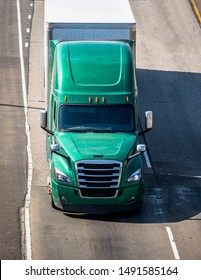 Big rig green long haul bonnet professional heavy-duty semi truck transporting commercial cargo in dry van semi trailer for delivery driving on the left line of wide multiline highway in sunny day