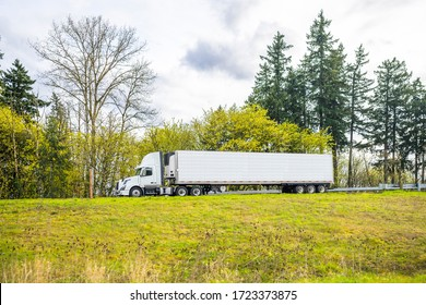 Big rig industrial day cab semi truck for local deliveries transporting frozen commercial cargo in refrigerator semi trailer running on the road up the hill with evergreen trees on the side