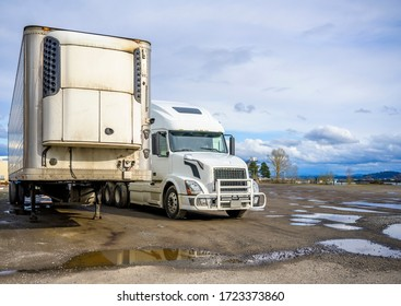 Big rig industrial diesel long haul semi truck with grille guard standing side by side with refrigerated semi trailer on the with parking lot with puddles waiting for the next load for delivery