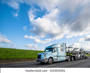 Big rig light blue long haulage car hauler semi truck with drivers rest compartment transporting different cars on the special two levels modular semi trailer driving on the flat road with green hill