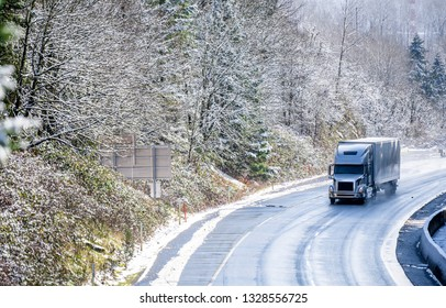 Big rig long haul gray semi truck tractor transporting commercial cargo in dry van semi trailer going on the wet slippery road with water from melting snow and winter snowy trees on the hills