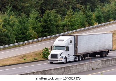 Big rig long haul popular white bonnet comfortable semi truck transporting frozen and chilled cargo in full size refrigerated semi trailer running on the multiline highway with downhill exit road