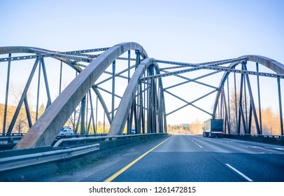 Big rig long haul semi truck transporting covered semi trailer with co commercial cargo driving on the winter frosty arched truss bridge with connected arches