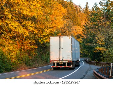 Big rig powerful American long haul semi truck transporting commercial cargo in dry van semi trailer with tree reflection driving on winding autumn colored road in Columbia River Gorge back view
