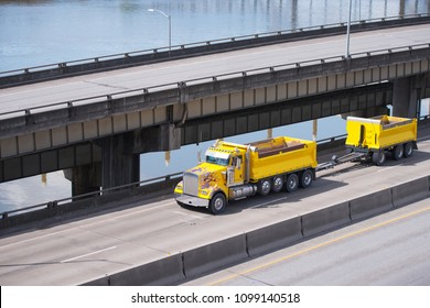 Big rig powerful classic yellow tipper semi truck with two dumps for carry more cargo running on overpass intersection road along the river and another elevated road on the side
