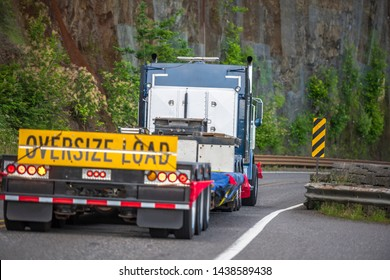 Big rig powerful heavy-duty semi truck tractor transporting oversized empty step down semi trailer with oversize load sign driving on the mountain road with rock wall
