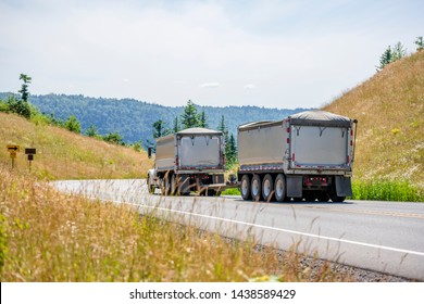 Big rig powerful industrial brown tipper semi tuck tractor with two dump trailers for heavy loads running on the winding road in green trees forest with hills in Columbia Gorge area