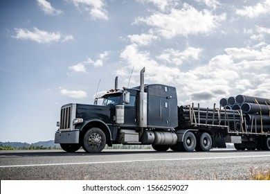 Big rig powerful professional industrial bonnet semi truck for long haul delivery commercial plastic pipes going with step down semi trailer on the summer road with green forest trees on the sides