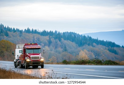 Big rig powerful red American bonnet semi tow truck with turned on headlights towing broken semi truck with roof spoiler on the winding evening twilight wet road with light reflection in rain weather