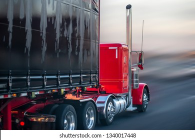 Big rig red American classic bonnet long hauler semi truck with rubberized fabric covered black semi trailer moving on wet raining road with rain dust blurry haze going to warehouse for loading