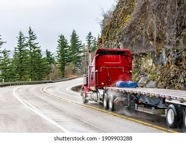 Big rig red semi truck with chrome pipes transporting empty flat bed semi trailer running on the winding wet road with rain dust driving on the bridge with rock cliff on the side in Columbia Gorge