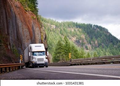 Big rig semi truck with refrigeration trailer transporting cargo moving on the bridge on a winding road with a rock wall on one side and a precipice on the other in Columbia Gorge national park area