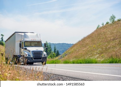 Big rig white day cab semi truck with roof spoiler transporting huge covered bulk semi trailer moving uphill on the turning winding road with yellow grass and green trees