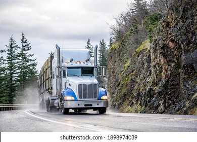 Big rig white semi truck with chrome pipes transporting commercial cargo on flat bed semi trailer running on the winding wet road with rain dust with rock cliff on the side in Columbia Gorge area