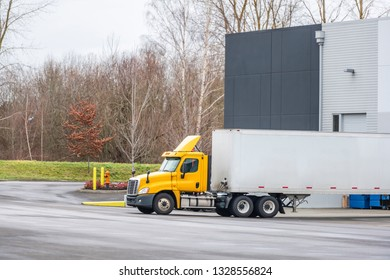 Big rig yellow day cab semi truck and dry van semi trailer standing in warehouse dock for loading and unloading commercial cargo and continuing go to the destination according to schedule